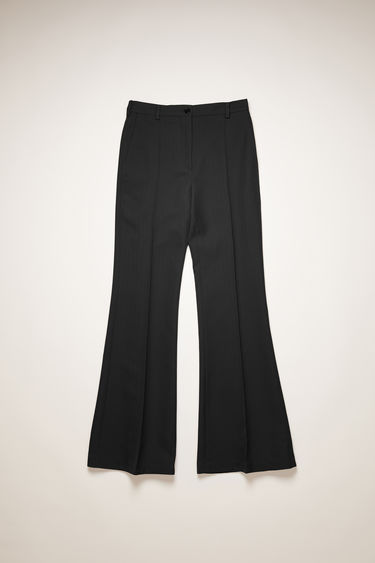 Acne Studios black trousers are cut to sit high on the waist that gradually flare out on the lower leg and is neatly finished with pressed creases down the front and back.