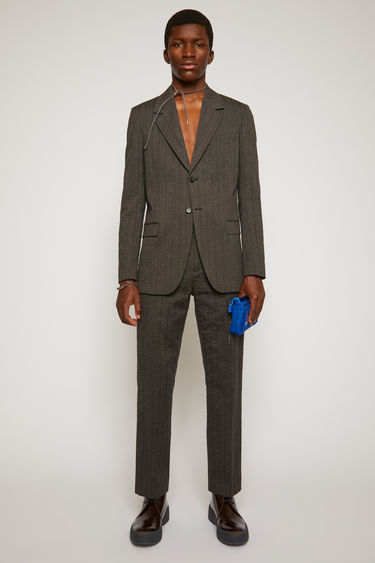 Acne Studios graphite/anthracite grey single-breasted jacket is made from a blend of virgin wool and cotton woven with tonal pinstripes. It's fully lined in satin and defined with notch lapels and lightly padded shoulders.