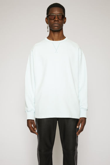 Acne Studios powder blue sweatshirt made from heavyweight brushed jersey that has been garment dyed for a soft, washed-out finish. It has a ribbed v-insert below the crew neck and a reversed logo printed across the chest.