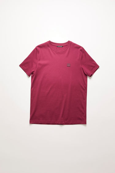 Acne Studios dark pink t-shirt is cut from a lightweight cotton jersey to a slim-fitting silhouette with a round neckline and accented with a tonal face-embroidered patch on the chest.