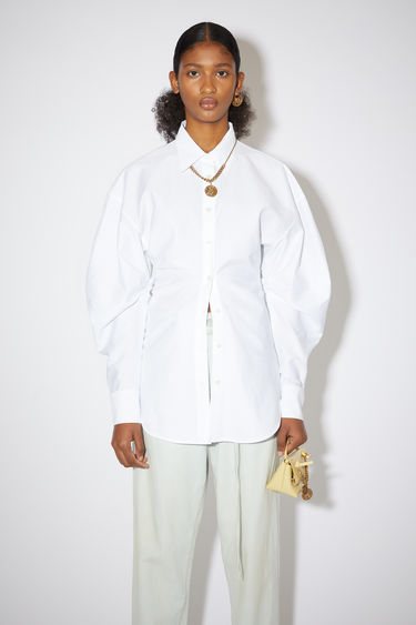 Acne Studios white shirt is made from mid-weight blended cotton and crafted with sculptural balloon sleeves, then cinched by the shirring at the waist. It's neatly shaped with a point collar and an elongated curved hem.