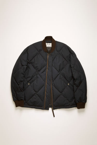 Acne Studios dark navy bomber jacket is quilted and filled with insulating down and feather and finished with a ribbed neck and cuffs.