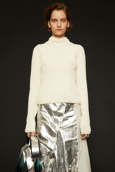 Acne Studios off white sweater is knitted in a full cardigan stitch with a mock neck and finished with rolled edges on the neck, cuffs and hem.