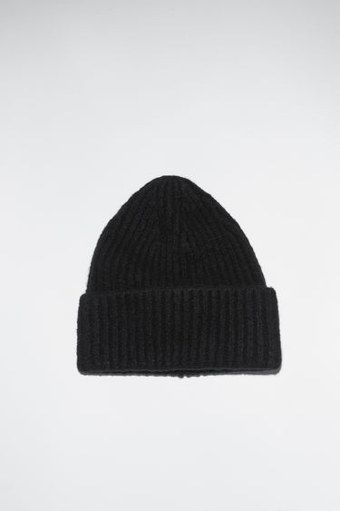 Acne Studios all black rib knit beanie hat is made of a cashmere blend with an upturned edge.