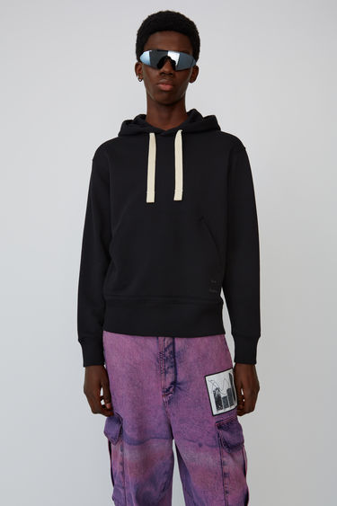 Acne Studios Fellis Logo black/ecru hooded sweatshirt is made from cotton fleece jersey and accented with a tonal logo on the front pocket.