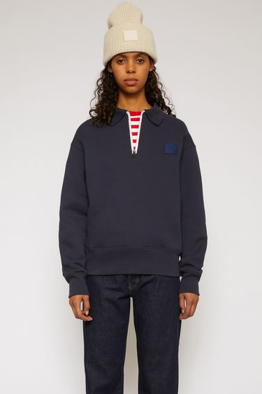 Acne Studios navy sweatshirt is crafted from heavyweight fleece jersey to an oversized silhouette with a contrasting half-zip closure and point collar and accented with a tonal face-embroidered patch on the chest.