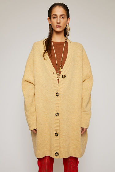 Acne Studios beige cardigan is knitted from lightweight Shetland wool and shaped to an oversized fit with a deep v-neck and dropped shoulder seams.