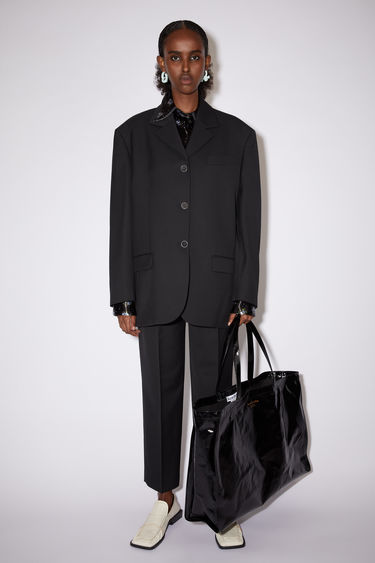 Acne Studios black single-breasted suit jacket is made of a wool blend with a very oversized fit.