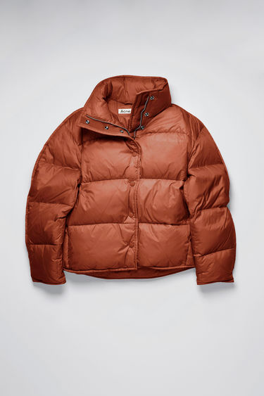 Acne Studios rust orange down jacket is padded with recycled down and feathers and is shaped to a cocoon silhouette with binding running along the edges. The funnel collar has a packaway hood and accented with a tonal logo print at the chest.
