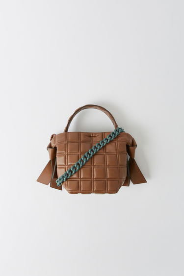 Acne Studios Musubi Mini chocolate brown is crafted with quilted lamb leather, featuring obi-inspired knot details and a shoulder chain strap.