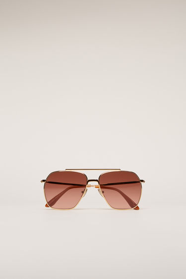 Acne Studios Anteom Gold/dark burgundy degrade sunglasses are shaped with squared aviator frames that are set with burgundy tinted lenses and then finished with acetate arm tips.