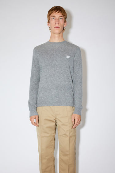 Acne Studios grey melange crew neck sweater is made from wool with a face logo patch and ribbed details.