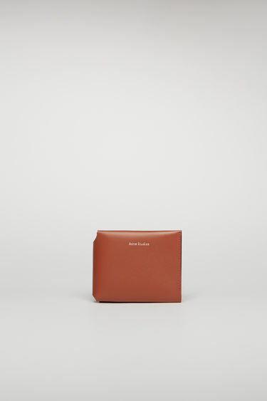 Acne Studios almond brown card wallet unfolds in three ways to reveal an internal coin pocket, four card slots and a slip pocket for notes.