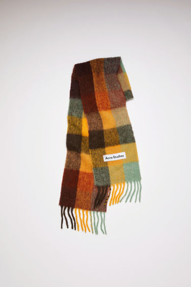 Acne Studios chestnut brown/yellow/green checked scarf is spun from alpaca, wool and mohair yarns to a wide dimension and features a stitched logo patch above the fringed edges.