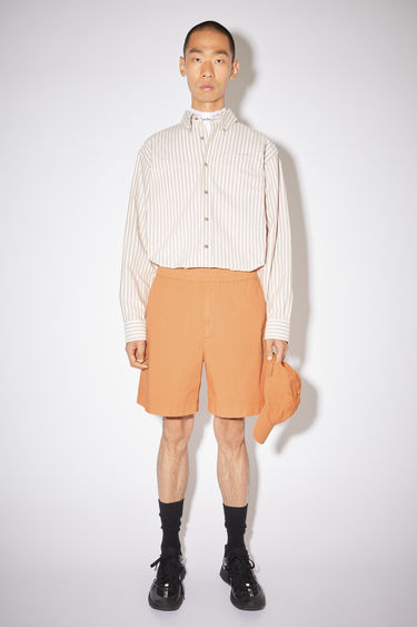 Acne Studios melon orange loose-fitting shorts are made of cotton with a logo at the back welt pocket.