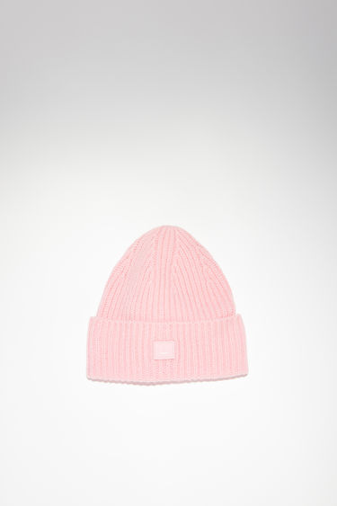 Acne Studios children's blush pink hat is made from rib knit wool with a face logo patch.