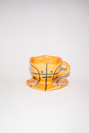 Acne Studios basketball cup and plate set is a limited edition collaboration with artist Bettunika, made in ceramic with inspiration from the Face collection.