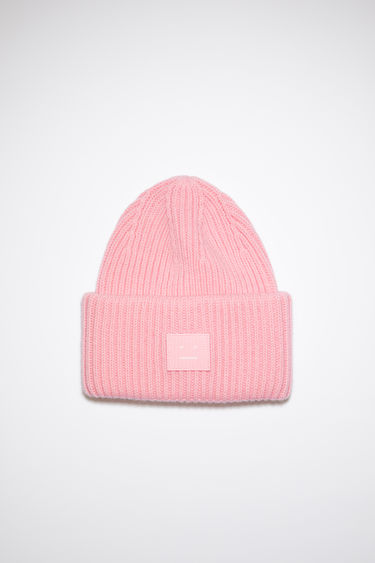 Acne Studios blush pink beanie hat is made from rib knit wool with a face logo patch.