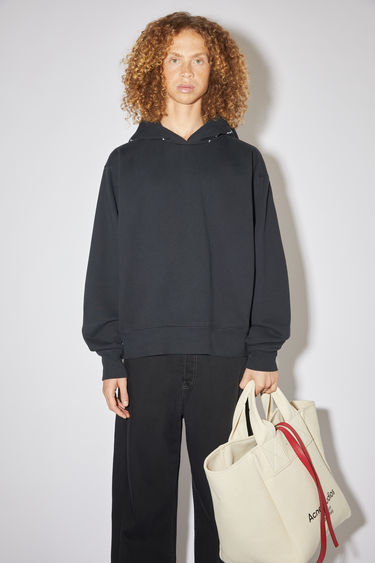 Acne Studios black sweatshirt is made from organically grown cotton and features the tonal logo along the drawstring hood. It's designed to fall loose over the frame with dropped shoulders.