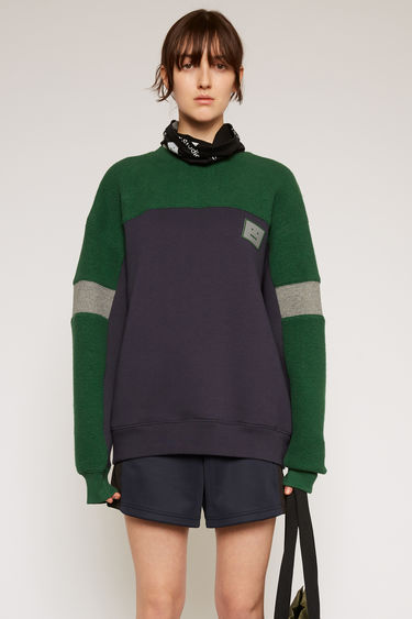Acne Studios navy sweatshirt is crafted to an oversized silhouette with a round neck and dropped shoulders and features contrasting panels of fleece and a rubber face-logo patch.