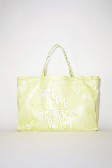 Acne Studios lemon yellow oilcloth tote bag features a Welcome to Stockholm graffiti print.