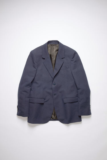 Acne Studios space blue constructed suit jacket is made of a cotton/linen blend with a classic fit.