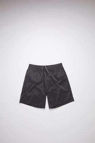 Acne Studios black swim trunks have pockets and a relaxed fit.