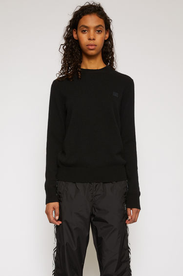 Acne Studios black sweater is knitted in a fine gauge from soft wool yarns and accented with a tonal face-embroidered patch on the chest.