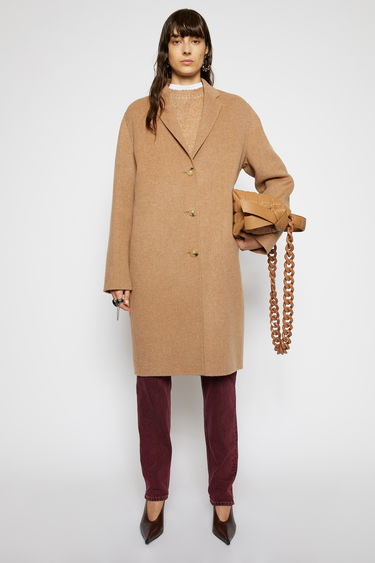 Acne Studios camel melange coat is crafted from double-faced wool to a relaxed silhouette and has notch lapels and three-button closure.