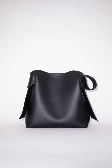 Acne Studios black large bag features twisted knots inspired by traditional Japanese obi sashes. It has a debossed logo and snap button closure, which opens to reveal a zipper compartment for storing small essentials.