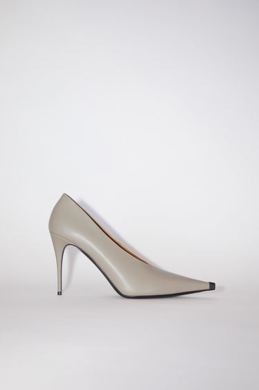 Acne Studios beige stiletto heel pumps are made of calf leather with long, pointed toes.