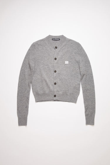 Acne Studios grey melange crew neck cardigan sweater is made from wool with a face logo patch and ribbed details.