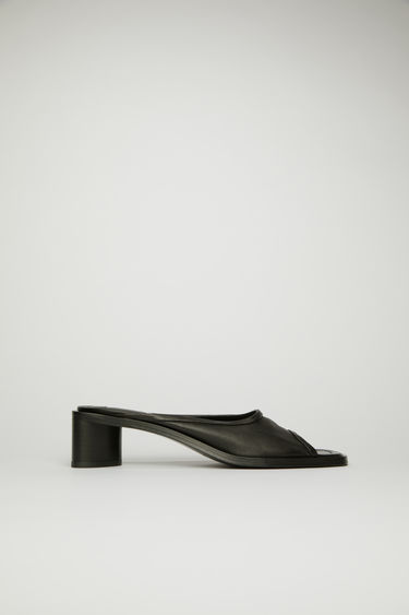 Acne Studios black/black open-toe mules are crafted from grained leather with a wide strap across the front, then set on a triangular block heel.