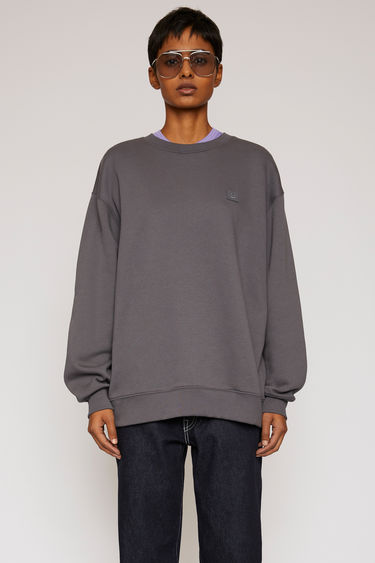 Acne Studios stone grey sweatshirt is crafted from midweight loopback fleece to a loose silhouette and finished with a face-embroidered patch on the chest.