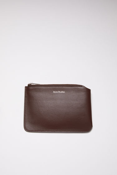 Acne Studios dark brown zip wallet is made of soft leather and accented with a silver-tone zipper closure and silver logo stamp on the front.