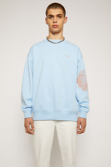 Acne Studios ice blue sweatshirt is crafted from organically grown cotton to an oversized fit and features a mandala-inspired print on one sleeve.