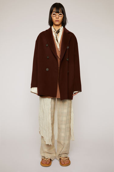 Acne Studios maroon red coat is crafted from double-faced wool to a relaxed silhouette with notch lapels, then fastens with a double breasted button closure.