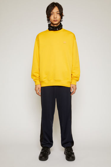 Acne Studios honey yellow sweatshirt is crafted from midweight loopback jersey to an oversized silhouette with dropped shoulders and accented with a tonal face-embroidered patch on the chest.