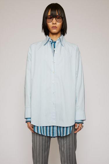 Acne Studios light blue shirt is made from lightweight cotton-poplin and is cut for a generous fit with a point collar, buttoned cuffs and a rounded hem.