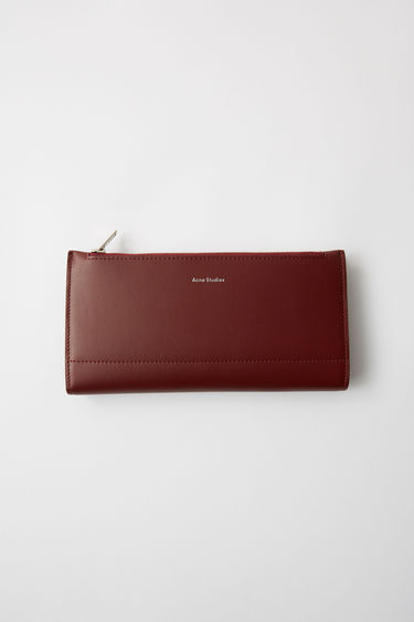 Acne Studios burgundy continental fold wallet, including zippered pouch and card holders.