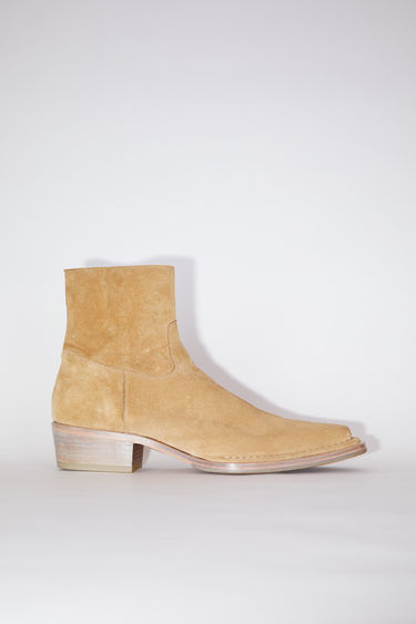 Acne Studios desert beige suede ankle boots are made of calf leather with pointed toes and zipper closures.