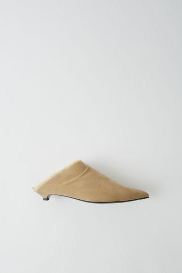 Acne Studios sand beige mules are crafted with soft suede to a point-toe silhouette and set on a mini heel.