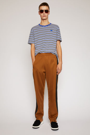 Acne Studios caramel brown lounge pants are crafted from technical jersey with an elasticated drawstring waist and trimmed with contrasting stripes down the sides.
