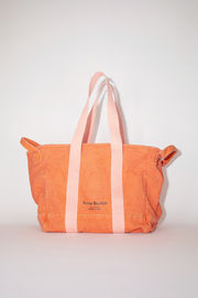 Acne Studios orange canvas tote bag is made of cotton with webbing shoulder straps and carrying handles.