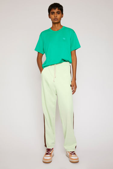 Acne Studios pastel green lounge pants are crafted from technical jersey with an elasticated drawstring waist and trimmed with contrasting stripes down the sides.