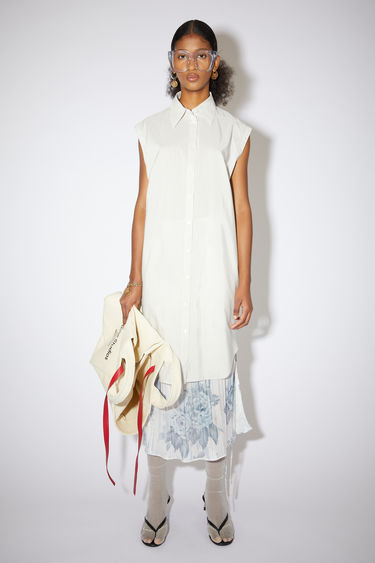 Acne Studios white/beige sleeveless shirt dress is made of a subtly striped cotton blend with a relaxed fit.