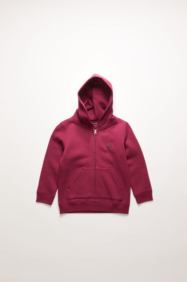 Acne Studios Mini Ferris Zip F dark pink is a hooded sweatshirt crafted from midweight brushed jersey with a zip-up front closure and kangaroo pockets and accented with a tonal face-embroidered patch on the chest.