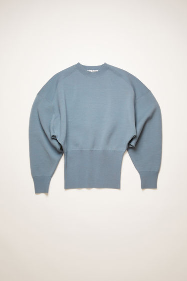 Acne Studios dusty blue sweater is knitted with voluminous dolman sleeves and features exaggereated ribbing on the fitted cuffs and hem to define the waistline.