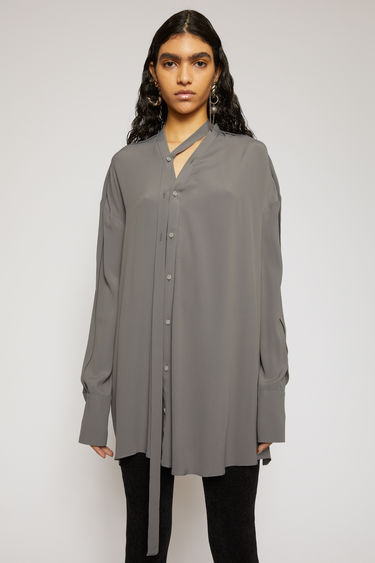 Acne Studios steel grey blouse is cut generously through the body with dropped shoulders and a v-neckline and features a draped button placket that's left to fall loosely through the front.