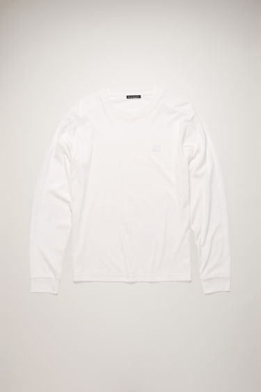 Acne Studios optic white t-shirt is crafted from lightweight cotton jersey to a relaxed shape with a round neck and long sleeves and accented with a tonal face-embroidered patch on the chest.